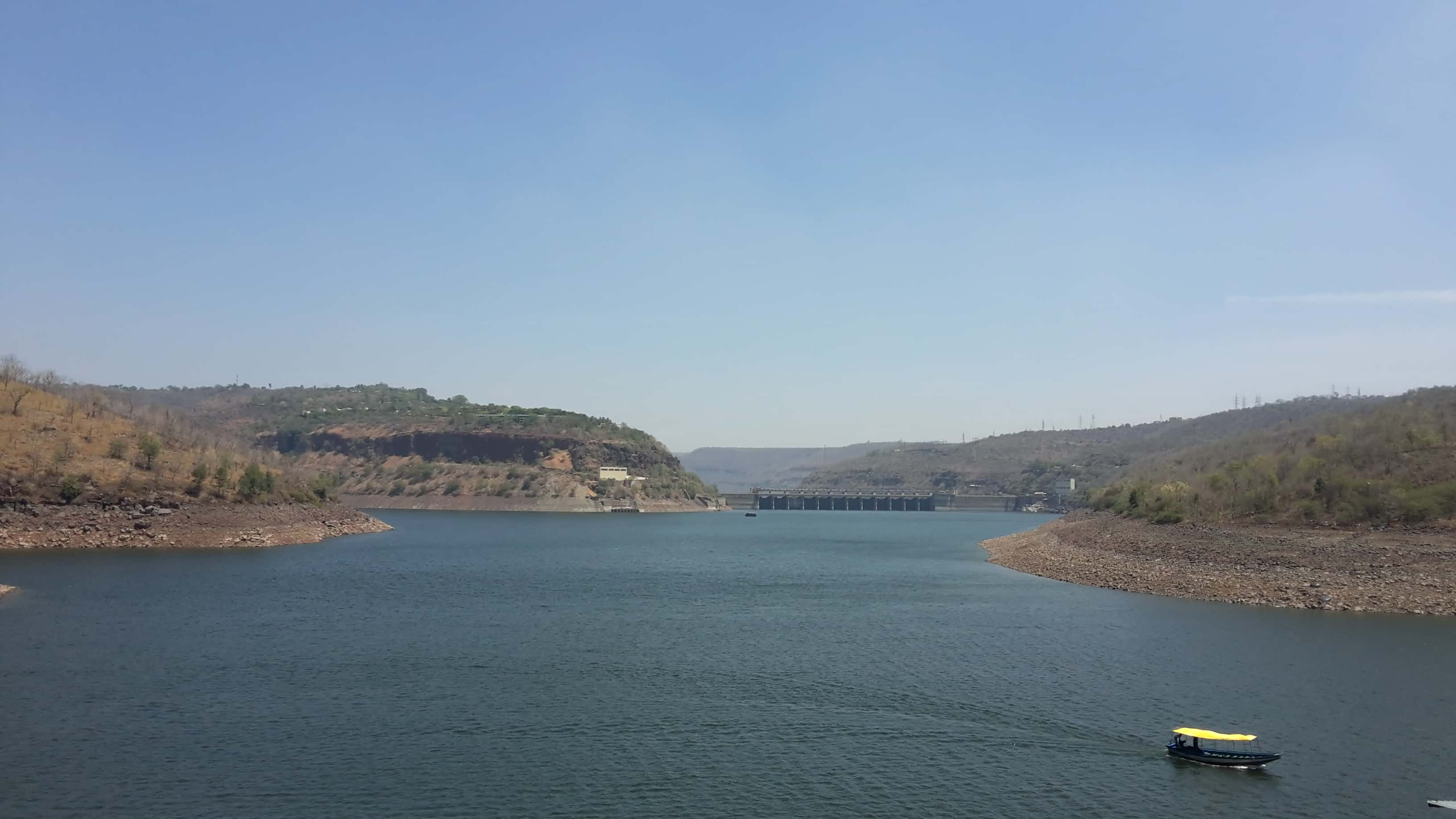 A yellow boat passing by near Srisailam Tiger Reserve area